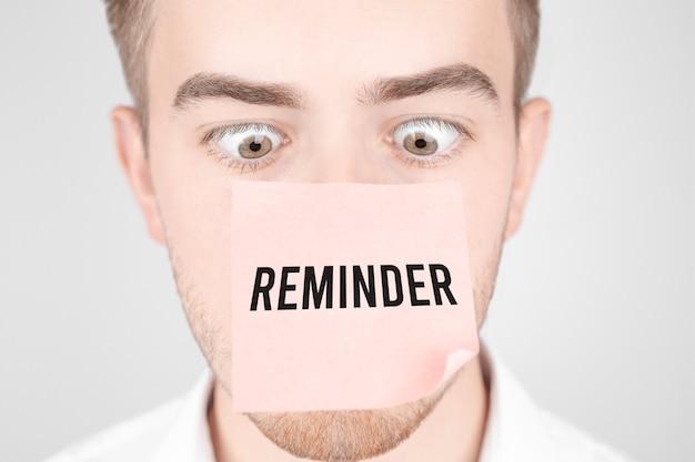 L'uomo con un adesivo rosso sul naso legge il testo promemoria