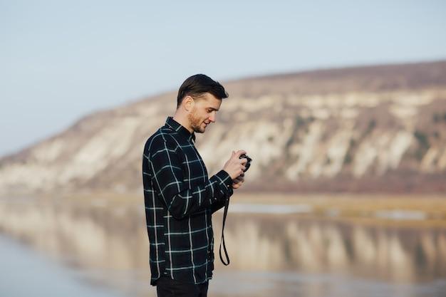 Uomo con una fotocamera retrò guarda le foto che scatta in montagna