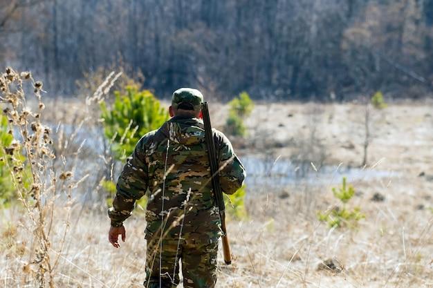 L'uomo con un fucile in abiti mimetici va nel bosco
