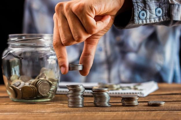 Uomo con le monete di risparmio sul barattolo