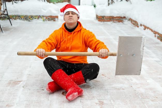 Un uomo con una pala per pulire la neve pronto a combattere la neve pulito il territorio siede nel loto