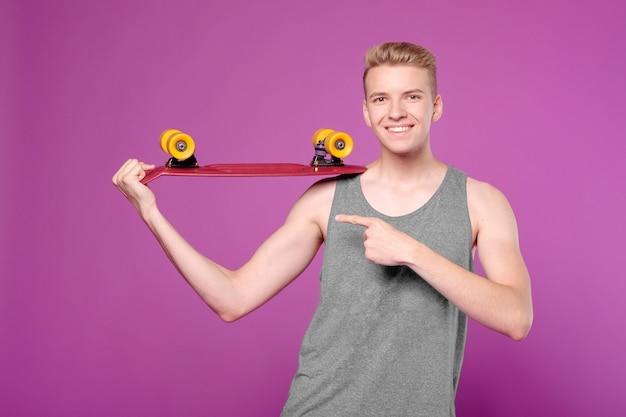Uomo con skateboard in mano su sfondo viola, penny little board