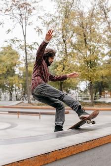 Uomo con lo skateboard all'aperto nel parco cittadino