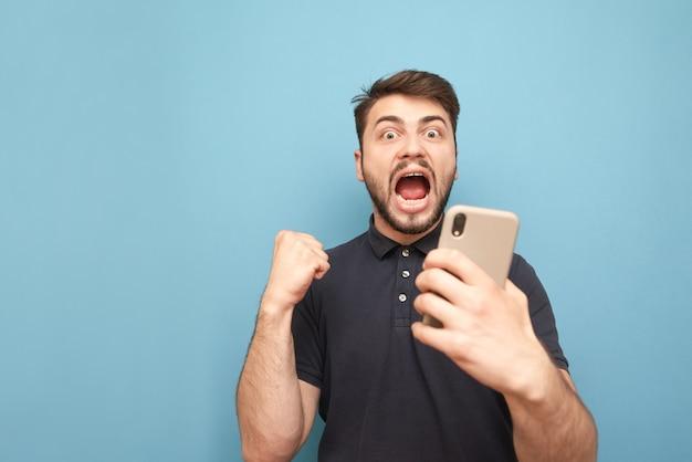 L'uomo con uno smartphone in mano esulta per il successo, isolato sull'azzurro