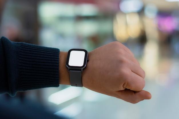 Un uomo con uno smartwatch e un mockup di schermo bianco in mano. un uomo utilizza un fitness tracker sullo sfondo di un centro commerciale.