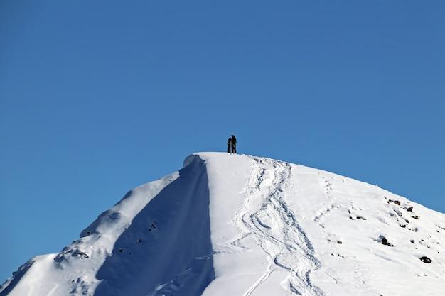 Uomo con lo snowboard in cima alla montagna innevata del caucaso
