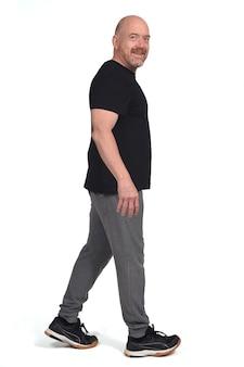 Uomo con abbigliamento sportivo che cammina su uno sfondo bianco