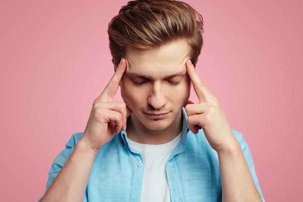 L'uomo che soffre di emicrania tiene le dita sulle tempie per rivelare il dolore