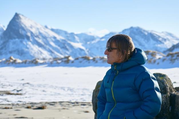 L'uomo con gli occhiali da sole guarda al lato. montagne innevate e spiaggia sullo sfondo.