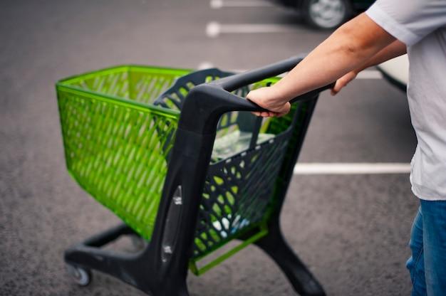 Uomo con un carrello del supermercato in un parcheggio in un parcheggio.