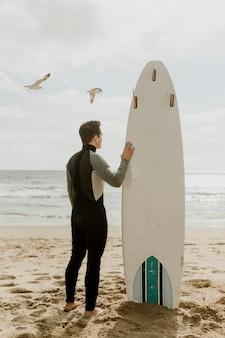 Uomo con una tavola da surf che guarda il mare