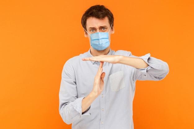 Uomo con maschera medica chirurgica in piedi con gesto di timeout e speranza per una pausa o più tempo