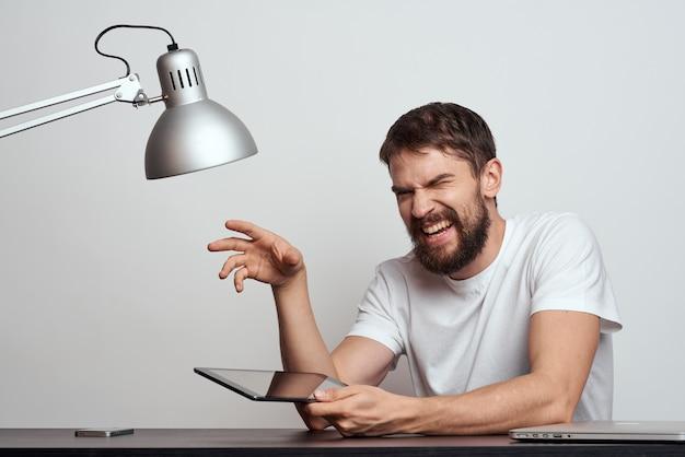 Un uomo con una tavoletta al tavolo gesticola con le mani su uno sfondo chiaro e una lampada di ferro. foto di alta qualità