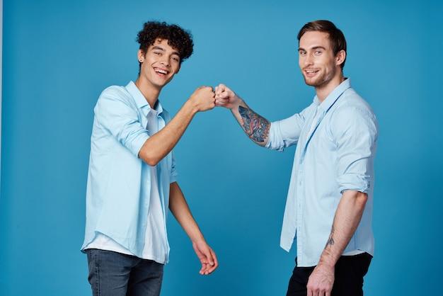 Un uomo con un tatuaggio stringe la mano a un ragazzo riccio su una comunicazione di amici di sfondo blu
