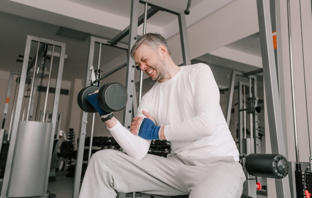 Un uomo con una faccia tesa solleva i manubri mentre è seduto su una panchina in palestra. bodybuilding principiante. sessioni di formazione intensiva