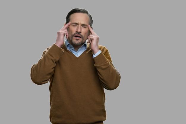 Uomo con un terribile mal di testa su sfondo grigio. uomo oberato di lavoro che soffre di emicrania. stanchezza e concetto di problema di salute.