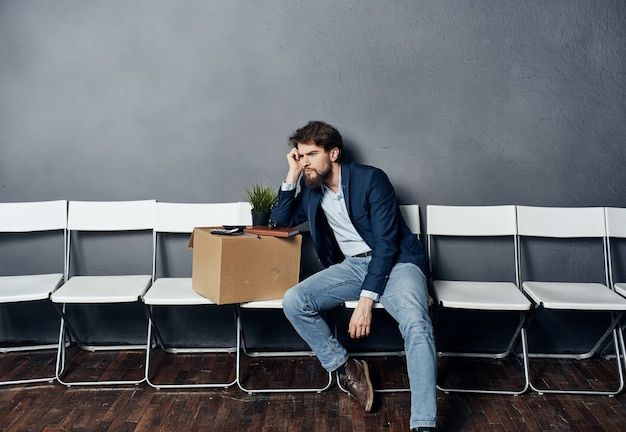 Un uomo con le cose in una scatola siede su una sedia in attesa del malcontento