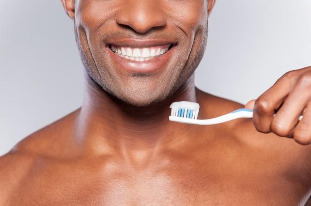 Uomo con spazzolino da denti. immagine ritagliata di un giovane africano senza camicia che tiene uno spazzolino da denti con dentifricio e sorride mentre sta in piedi su uno sfondo grigio