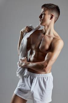 Uomo con un asciugamano in pantaloncini bianchi atleta bodybuilder muro isolato.