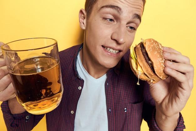 Uomo con un vassoio di cibo spazzatura: hamburger e patatine fritte, birra