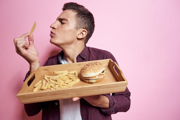 Uomo con un vassoio di cibo spazzatura