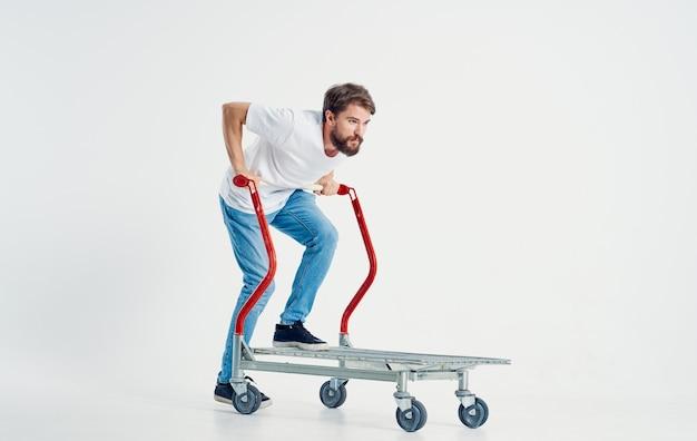 Uomo con un carrello in mano su uno spazio leggero che trasporta oggetti pesanti
