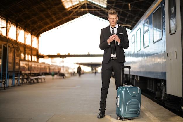 Uomo con carrello nella stazione ferroviaria