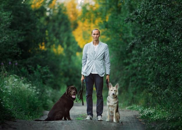 Un uomo con due cani che cammina su un prato soleggiato