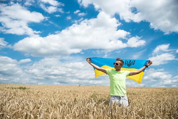 Uomo con bandiera ucraina sul campo di grano in estate. stile di vita