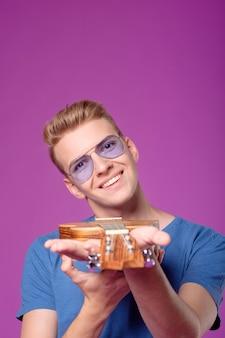 Uomo con ukulele in mano su sfondo viola