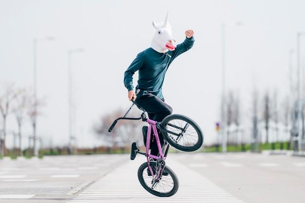 Uomo con maschera di unicorno in sella a una bicicletta