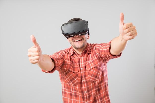 Uomo con i vetri di realtà virtuale che mostra pollice in su