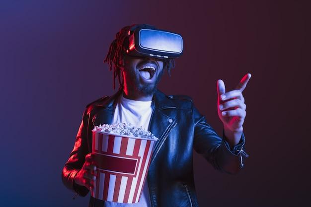 Un uomo con occhiali vr e popcorn guarda un film in 3d