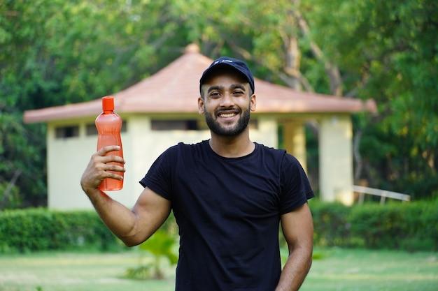 Un uomo con una bottiglia d'acqua nel parco