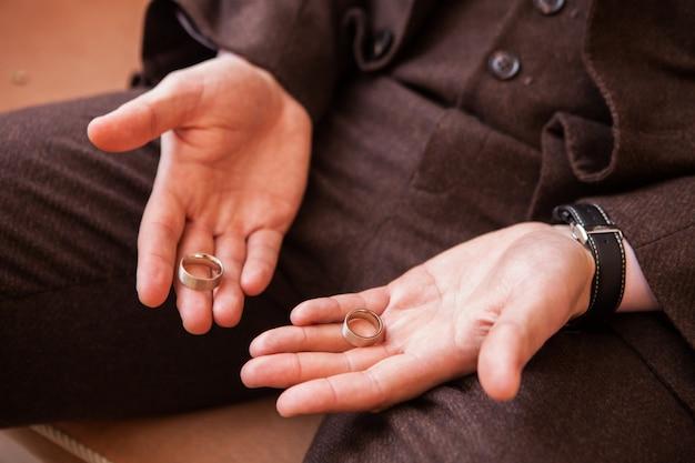Uomo con un anello di nozze. sposo che tiene due anelli sul palmo