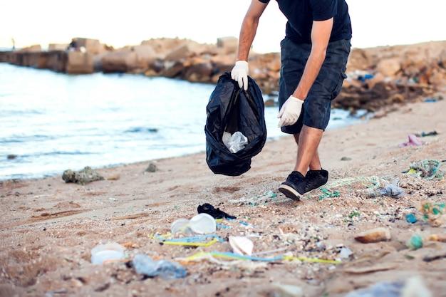 Uomo con guanti bianchi e grande pacchetto nero che raccoglie immondizia sulla spiaggia. protezione ambientale e concetto di inquinamento del pianeta