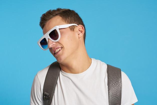 Uomo con occhiali da sole bianchi su sfondo blu