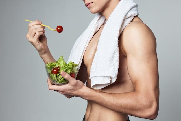 Uomo con un asciugamano bianco sulle spalle piatto di insalata cibo sano isolato muro