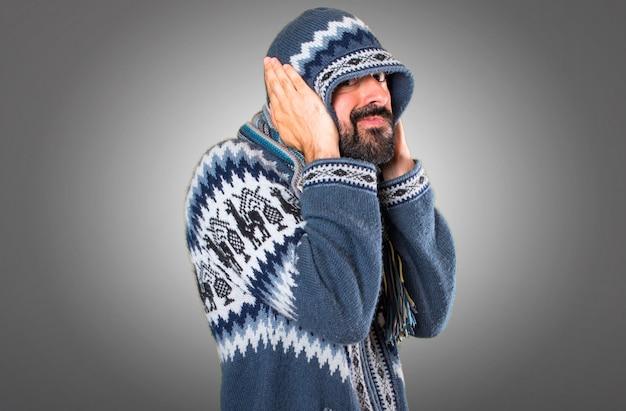Uomo con abiti invernali che coprono le orecchie su sfondo grigio