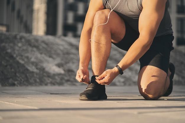 Un uomo con le cuffie cablate in una leggera uniforme atletica lega un laccio a una scarpa per correre