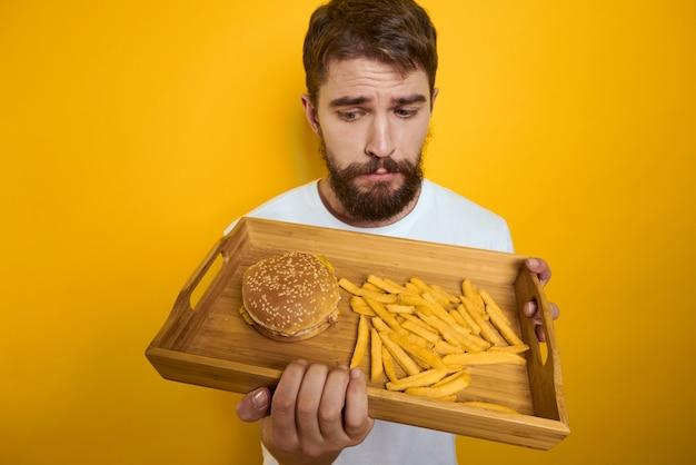 Uomo con pallet di legno fast food hamburger patatine fritte dieta assunzione di cibo