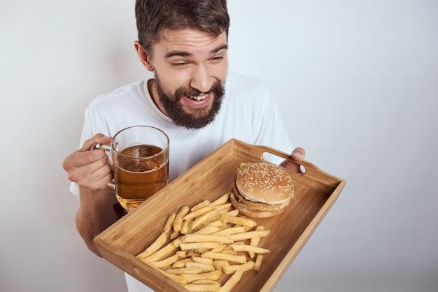 Uomo con vassoio in legno boccale di birra patatine fritte hamburger modello calorie fast food e t-shirt bianca