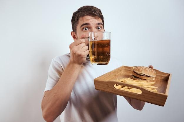 Uomo con vassoio in legno, boccale di birra, patatine fritte e hamburger