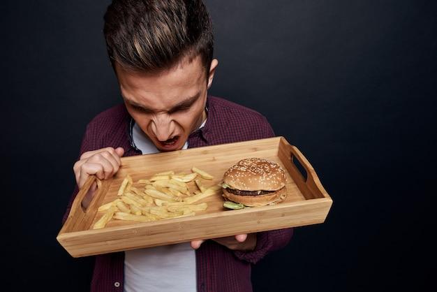 Uomo con vassoio in legno di fast food