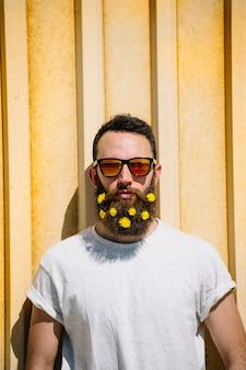 Uomo con fiori gialli nella barba