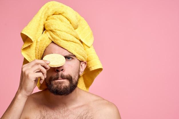 Uomo con l'asciugamano giallo sulla sua testa rosa spugna per la cura della pelle pulita
