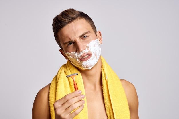 Un uomo con un asciugamano giallo sulle spalle e una pelle pulita di schiuma bianca come un rasoio.