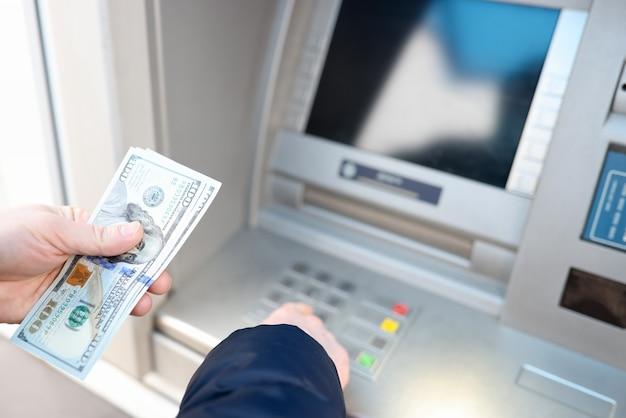Uomo che ritira dollari americani dal primo piano atm. concetto di servizi bancari