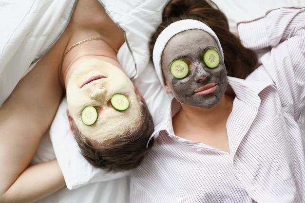 L'uomo e la donna applicano una maschera all'argilla per il ringiovanimento sul viso e i cetrioli sugli occhi