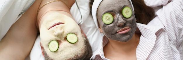L'uomo e la donna applicano la maschera di argilla per il ringiovanimento sul viso e i cetrioli sugli occhi